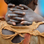 A boy in rags stands with his hands behind his neck at a   child registration in Gasorwe ADP.